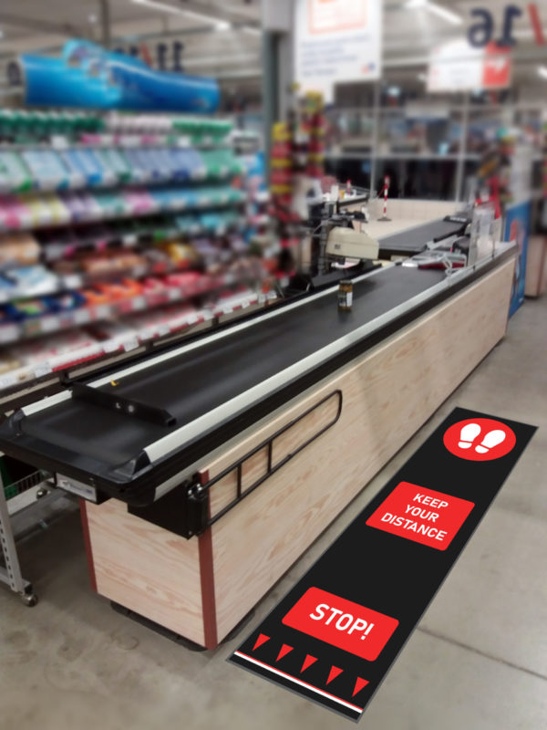 Red Social distancing mat beside counter at supermarket