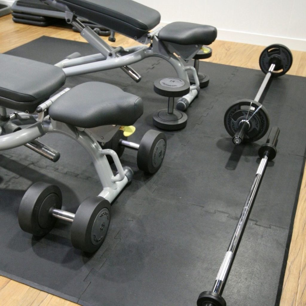 Benches and free weights on interlocking gym tiles.