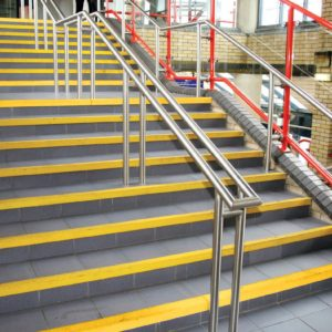 Yellow grippy stair nosings on large set of stair edges
