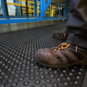Man standing on Bubbled Detailed Anti-Fatigue Interlocking Tiles