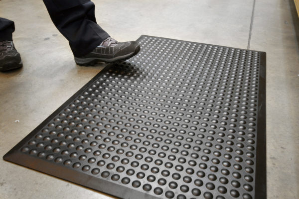 Person stepping on a black Bubbled Detailed Mat