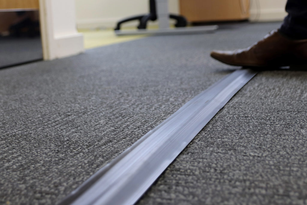 Man walking over cable protector pro in hard office shoes