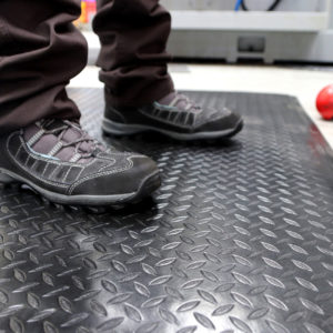 Man standing on a black and yellow deluxe workplace mat