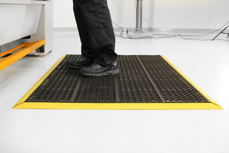 Man standing on a black and yellow deluxe workplace anti-fatigue mat