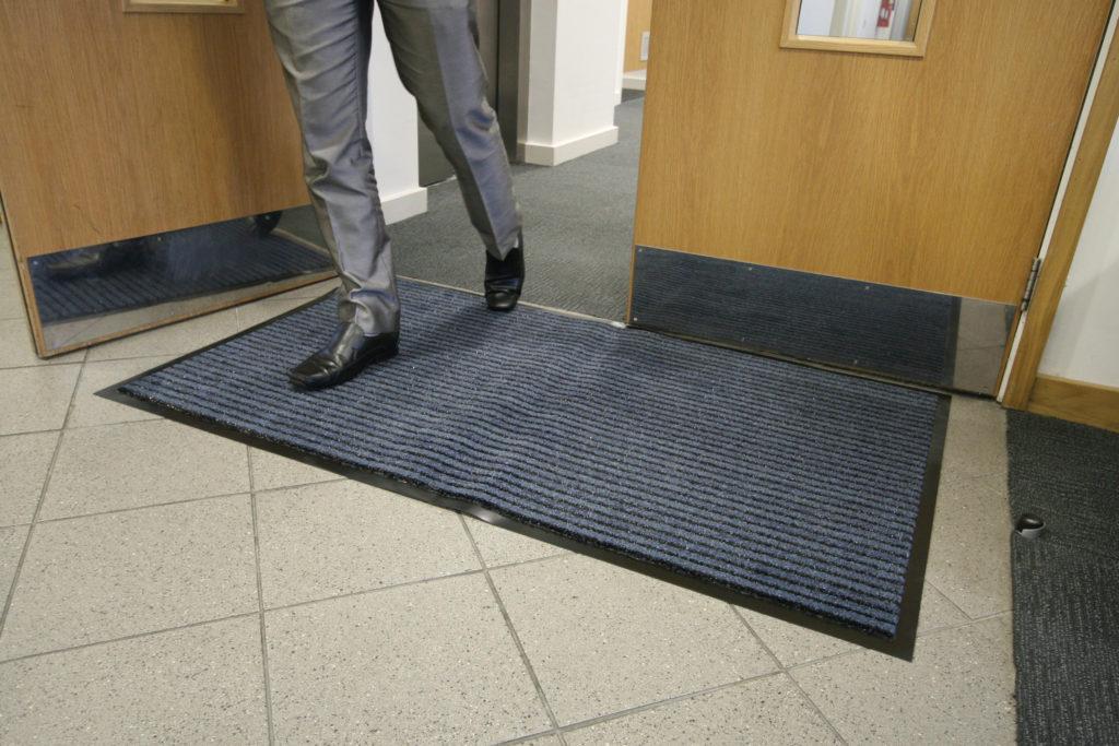 Man walking through doors ontop of a Blue/Black Double Action Doormat