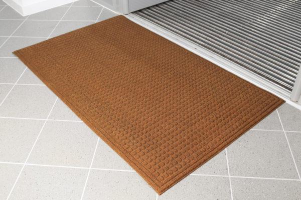 Brown eco-doormat beside an entrance