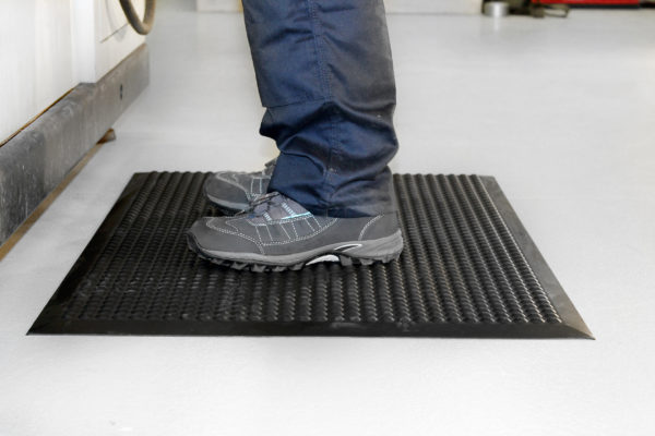 Woman standing on a black Electrostatic Discharge Mat