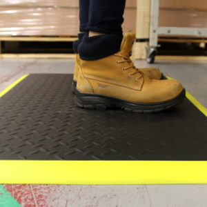 Woman standing on a black and yellow Electrostatic Discharge Mat with Diamond detailing