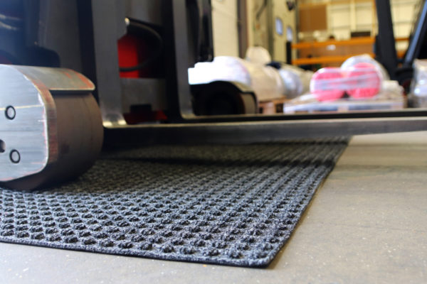 Close up image of grey Heavy High Performance Superdry Doormat on a carpet