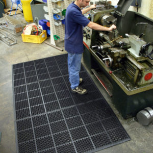 Man working machines whilst on a black mat