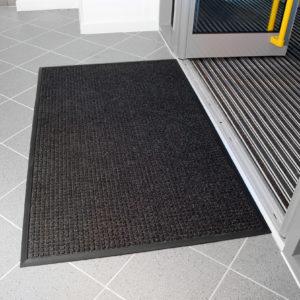 Black High Performance Superdry Doormat outside a building entrance