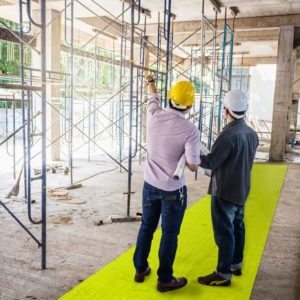 Builders stood on high visibility path at construction site