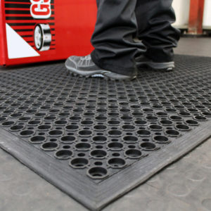 Man standing on a black Honeycombed Detailing mat