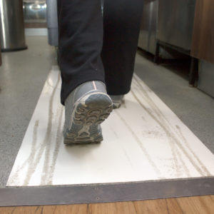 Person walking with a trolley on a sheet that captures dirt and mud