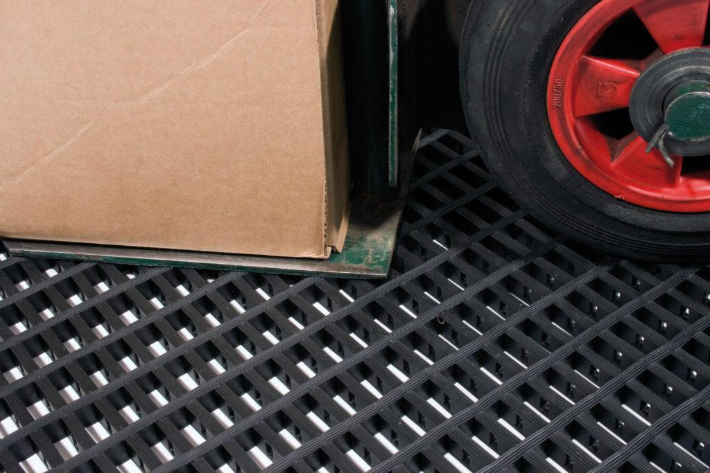 Wheeled trolley on a black medium duty woven PVC anti-fatigue mat