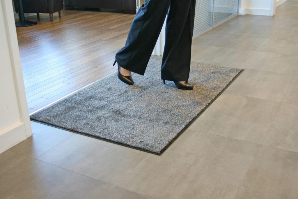 Woman walking on a beige microfibre washable doormat in high heels