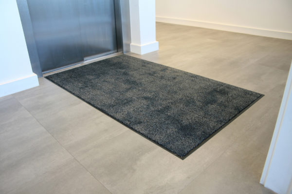 Black microfibre washable doormat outside an elevator