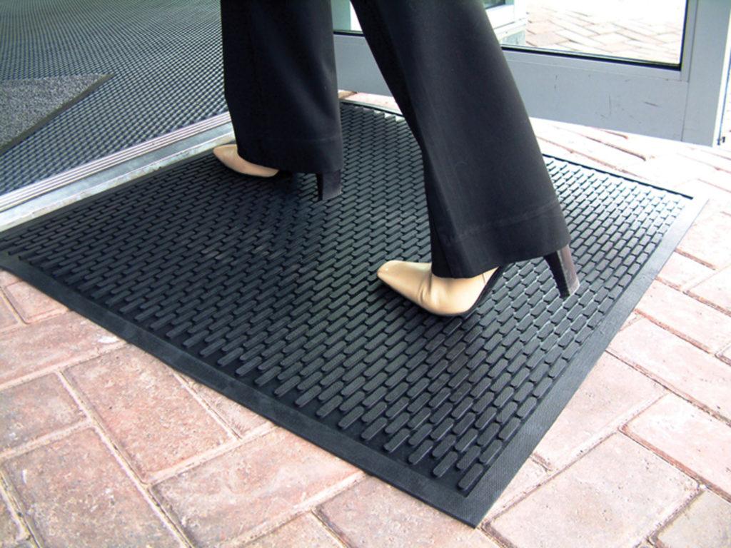 Woman standing on an outdoor entrance mat