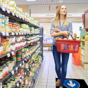 Woman following the direction of a one way arrow mat in supermarket