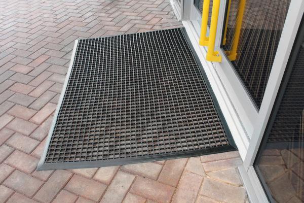 Black entrance mat outside a double window