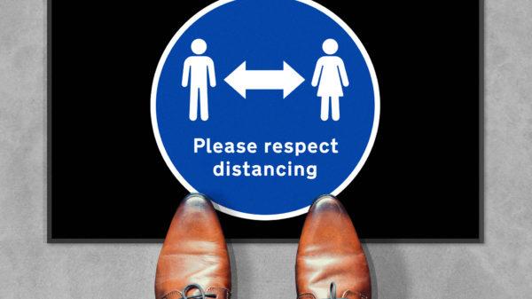 Man standing next to Please Respect Distancing Mat
