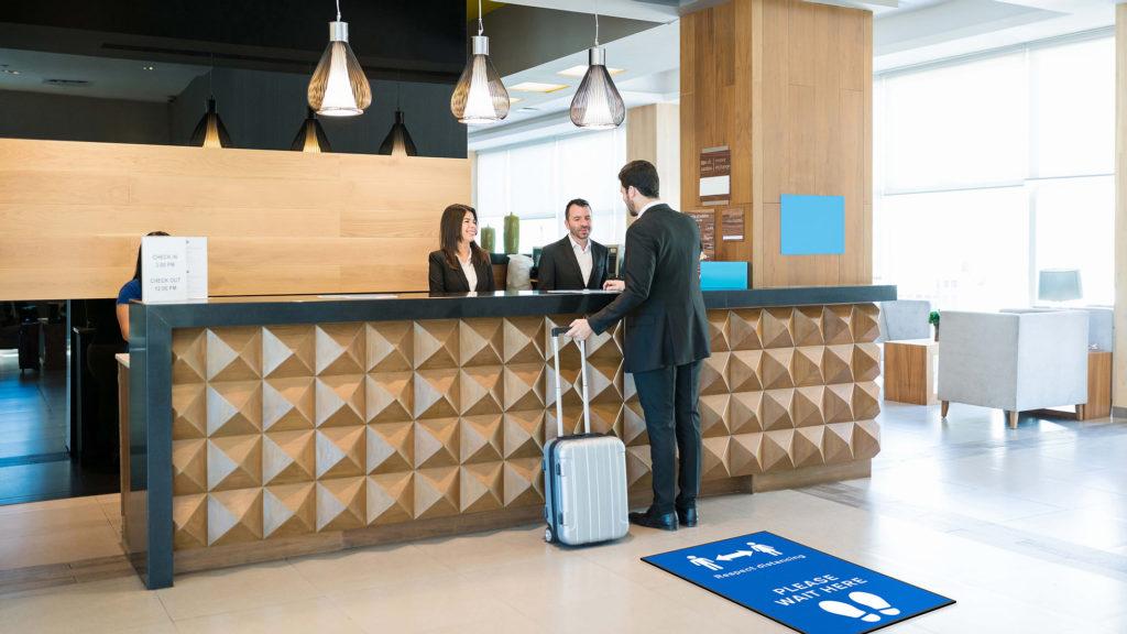 Man standing at a desk next to a blue social distancing mat