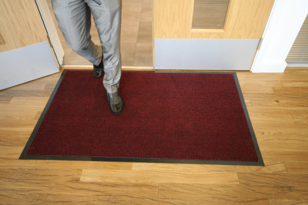 Man walking inside on a red plush doormat