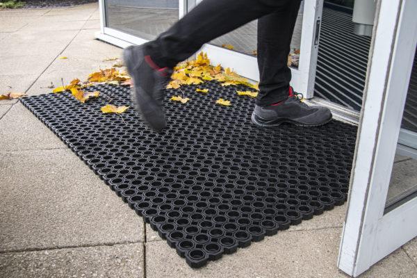 Woman walking on tough rubber outdoor mat