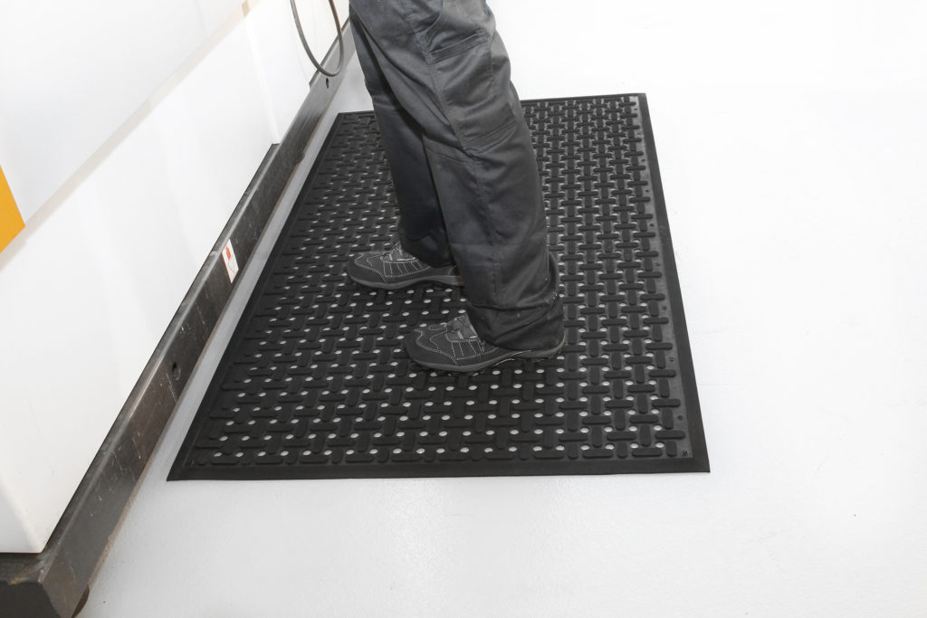 Person standing on black Rubber Anti-Fatigue mat with X detailing