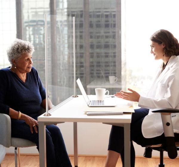 Women talking between a safety screen