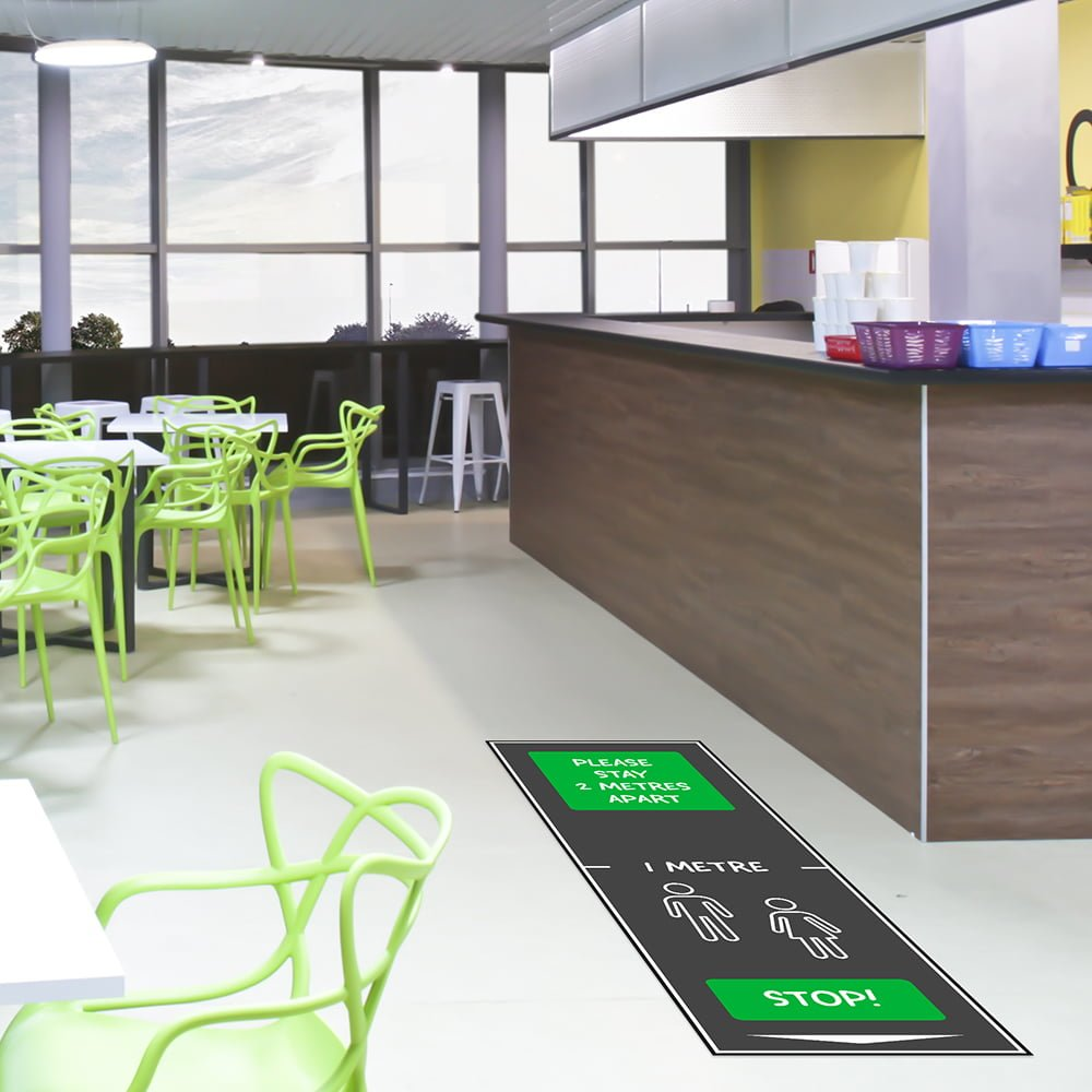 Green 'please stay 2 metres apart' mat in cafeteria