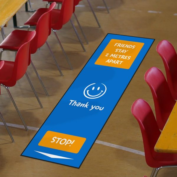 Blue and orange 'friends state 2 metres apart' mat around classroom chairs