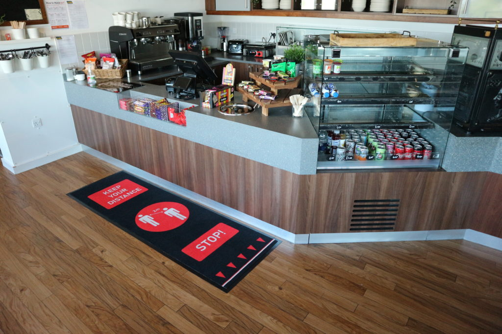 Red Social Distancing Mat by a cafe counter
