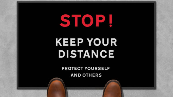 man standing next to 'stop and keep your distance' mat
