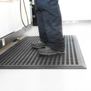 Person standing on a black Worksafe mat at workstation