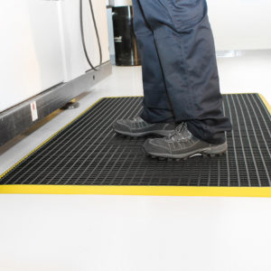 Man standing on black and yellow Workstation mat