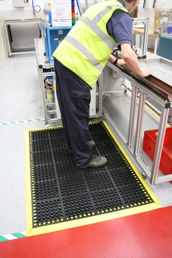 Man stood at a workstation on a black/yellow deluxe workplace mat