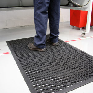 Man standing at work station on an Outdoor Rampmat