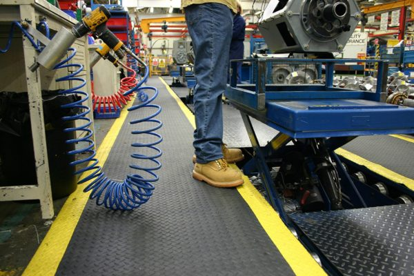 Man standing on a roll of Safety Diamond Detailing Mat