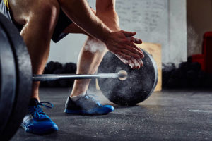 Man preparing to lift weights on a gym mat