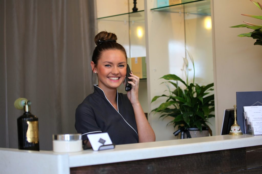 Receptionist at a spa with a smile talking on the phone